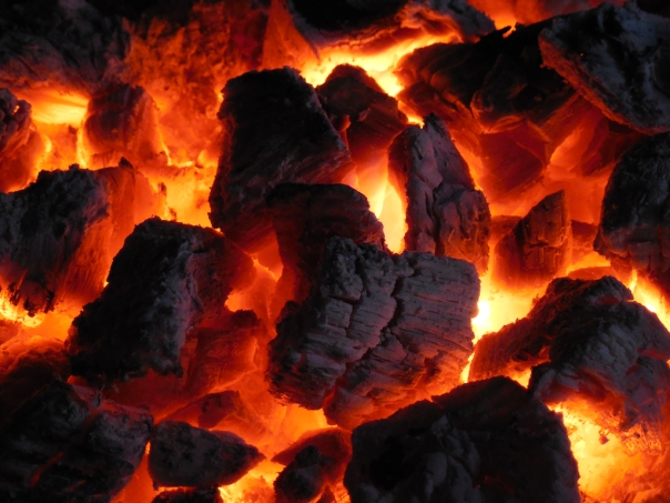 As the fire died down to embers, and the crackle quieted to a murmur, the remaining wood chips were lit up in the remains of the fire's fierce glow.